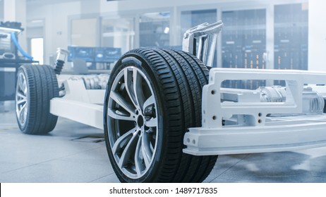 Concept of Authentic Electric Car Platform Chassis Prototype Standing in High Tech Industrial Machinery Design Laboratory. Hybrid Frame include Tires, Suspension, Engine and Battery.