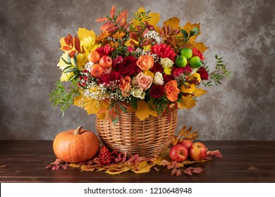 Concept of autumn. Bouquet of beautiful flowers in a basket, pumpkin and yellow leaves.