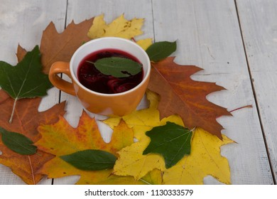 Concept of autumn comfort - colorful leaves and cup of tea on white wooden background. Top view