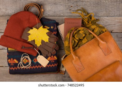 The concept of autumn holidays - bag, maple leaves, passport, key with blank label, warm clothes: a hat, scarf, pullover and gloves on a brown wooden background