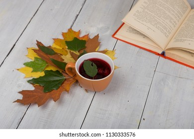 Concept of autumn resting - cup of tea with autumn colorful leaves and book on white wooden table