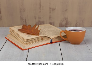 Concept of autumn resting - cup of tea with autumn colorful leaves and book on white wooden table and brown background