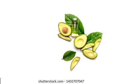 Concept of avocado oil, top view on a bottle with oil, freshly cut avocado fruit and green avocado leaves, blank space for a text