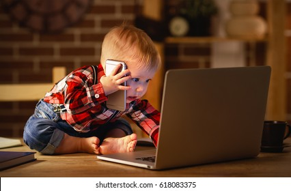 concept of baby boy working on a computer and talking on the phone