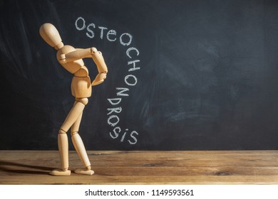 Concept of back pain. A wooden figure depicts a pain in the back. The inscription on a chalkboard osteochondrosis.