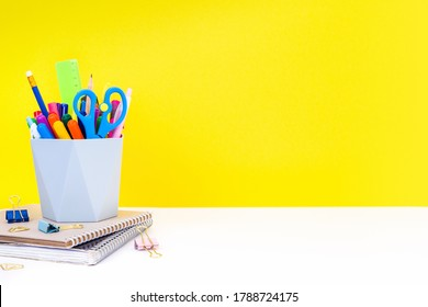 The concept of back to school, education - notebooks, stationery and organizer with multi-colored pens, felt-tip pens, pencils and scissors on a white table on a yellow background with copy space.