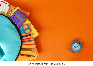 Concept back to school. Full turquoise School Backpack with supplies and alarm, notebook on orange background. FLat lay.