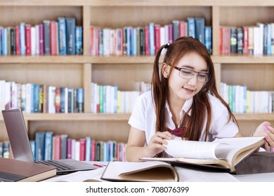 Concept of Back to School. Portrait of a pretty teenage student learns in the library while wearing glasses and reading books