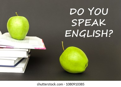 concept back to school, text do you speak english, two green apples, open books on gray background