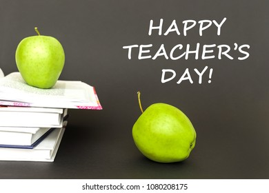 concept back to school, text happy teacher's day, two green apples, open books on gray background