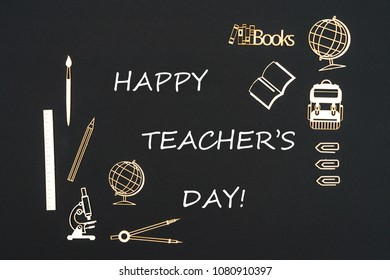 Concept back to school, text happy teacher's day with school supplies chipboard miniatures placed on blackboard