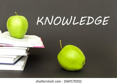 concept back to school, text knowledge, two green apples, open books on gray background