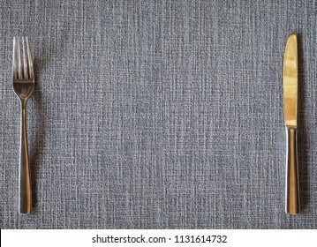 Concept of the background for the cover of the restaurant menu. A fork and knife of white metal on a gray homespun tablecloth with a pronounced texture of the fabric.