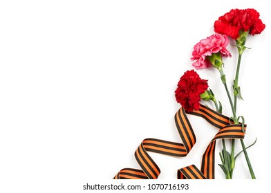 Concept background of May 9 russian holiday Victory Day. Red carnations and St. George's ribbon isolated on white background. Flat lay, copy space