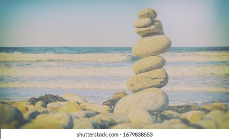 Concept of balance. Pebble stack on Pebble Beach (California), with ocean waves in the background.