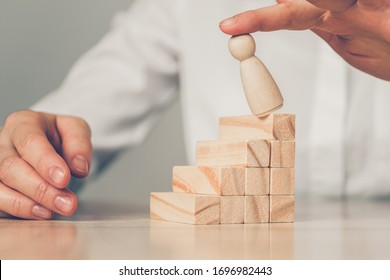 Concept Bankrupt businessman - hand blows abstract figure of a man with a ladder of wooden blocks. Close up.