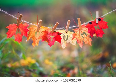 concept with a banner with the name and the word autumn carved on red maple leaves hang on clothespins and rope in the autumn sunshine Park