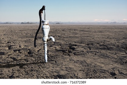 A concept of a barren, cracked, dry landscape with a single rusted water pump.