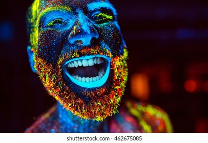 Concept. A bearded man smiles. Portrait of a bearded man painted in fluorescent powder.