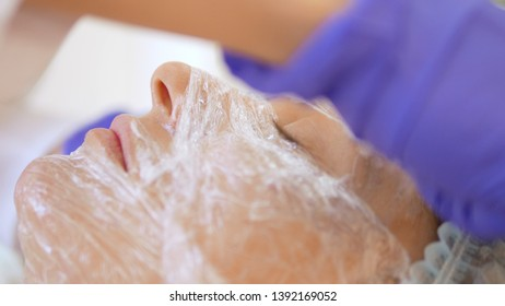 The concept of a beautician. The hands of a cosmetologist put a film on the face of a woman. anesthesia before the procedure of mesotherapy, biorevitalization or contour plastics