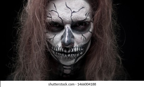 concept, beautiful makeup for halloween. Portrait of a young sexy girl with skull makeup. on a black background, face in the dark. close-up