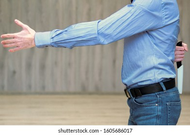 The concept of betrayal business. businessman holds out his hand for a handshake and holds a knife behind his back