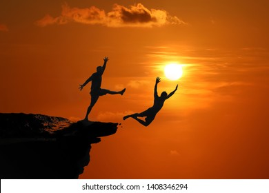 The concept of betrayal and the help of friends, Silhouette of Men are jumped between high cliff at a red sky sunset background