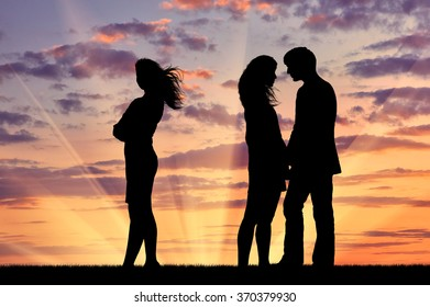 Concept of betrayal and treason. Silhouette of a lonely woman near loving couple at sunset