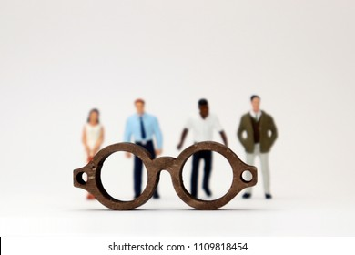 The concept of biased views judged by appearances. Various miniature people standing behind the glasses.