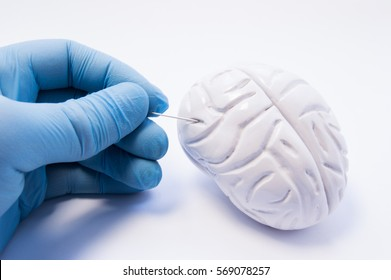 Concept of biopsy of brain tissue. Surgeon holding puncture needle and is preparing to puncture of the brain to capture nerve cells. Invasive diagnosis of brain diseases such as Parkinson's disease