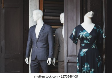 A concept of bisexuality. Two male mannequins stand near each other in the door opening looking as disturbed people and a mysterious woman mannequin (blurred) without the face hides behind the corner.