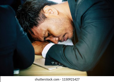 Concept, body fatigue : Businessman tired of falling asleep during a meeting in the office.
