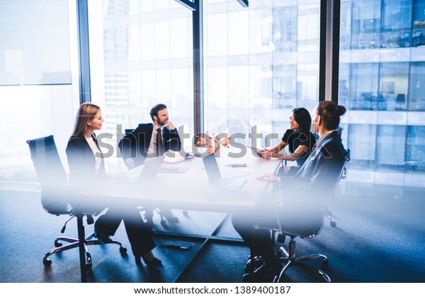 Concept of brainstorming and briefing, positive diverse male and female financial experts discussing information during working time in conference room sitting at desktop with laptop devices