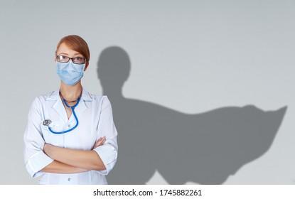 Concept of brave medical doctors in uniform and mask with shade of fluttering cape behind her shoulder.