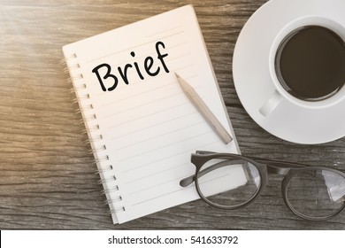 Concept Brief on notebook with glasses, pencil and coffee cup on wooden table. - Shutterstock ID 541633792