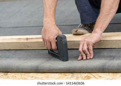 Concept of building construction industry. Close up photo of qualified and mature builder using stapler and working with special waterproof bitumen membrane. Man on rooftop of new modern house