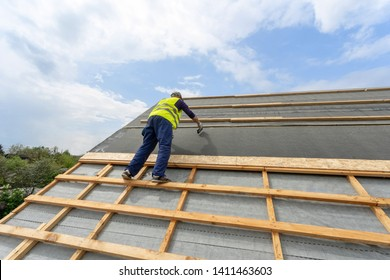 Concept of building construction industry. professional and qualified installer in protective uniform wear using stapler on rooftop with bitumen and waterproof membrane covering of new modern house