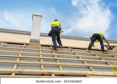Concept of building construction industry. Two unrecognizable, mature and professional specialist standing near chimney on rooftop of new modern house. They repair and fixing frame work on roof