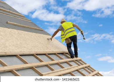 Concept of building construction industry. Unrecognizable qualified and mature contractor in protective uniform wear standing with hammer on roof top of new modern house against blue sky on background