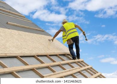 Konzept der Bauindustrie. Unerkennbarer qualifizierter und reifer Auftragnehmer in Schutzgleichgetragen mit Hammer auf dem Dach eines neuen modernen Hauses auf blauem Himmel auf Hintergrund