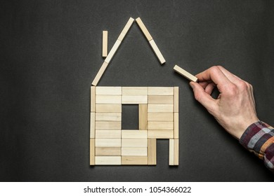 The concept of building a house in the form of wooden blocks. The hand of the man, the architect completes the frame of the design house.