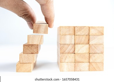 Concept of building success foundation,  Man's hand stack wooden blocks in the shape of stair to reach top goal.