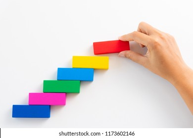 Concept of building success foundation. Women hand put red wooden block on colorful wooden blocks in the shape of a staircase.