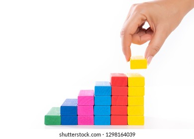 Concept of building success foundation. Women hand put wooden blocks in the shape of a staircase.