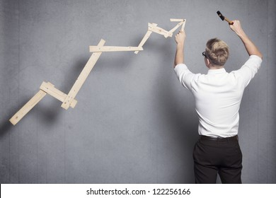 Concept: Building your own career or business. Young businessman installing upward arrow on floating business graph with positive trend, isolated on grey background.