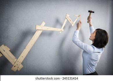 Concept: Building your own career or business. Young businesswoman installing upward arrow on floating business graph with positive trend, isolated on grey background