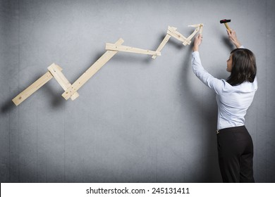 Concept: Building your own successful career or business. Confident businesswoman with hammer in hand building  business graph with positive trend, isolated on grey background.