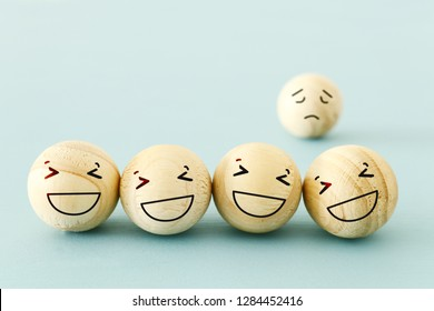 concept of bullying , discrimination. group of laughing emoticon faces and one alone look sad and depressed.