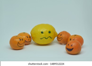concept of bullying , discrimination. group of laughing emoticon faces and one alone look sad and depressed. Lemmons and mandarines