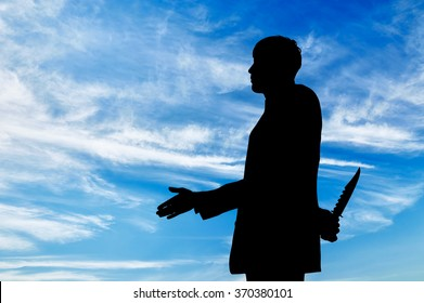 Concept of business betrayal. Silhouette of a businessman shaking hands and holding a knife behind his back
